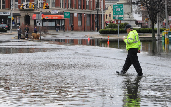 Peabody:<br /> David Bettencourt, of the DPW, walks through the high water on Central Street in Peabody Square.<br /> Photo by Ken Yuszkus/Salem News, Wednesday, March 31, 2010.