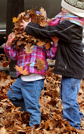 Salem:<br /> Aidan Blot, 5, throws a handful of leaves into the face of his sister, Sawyer Call, 2, while playing in the fallen leaves at Salem Common on Monday afternoon. Aidan and Sawyer are from Salem.<br /> Photo by Ken Yuszkus/Salem News, Monday, November 21, 2011.