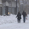 Danvers:<br /> Cindy Sonia and Michael Fox walk along Elm Street taking photographs during the snowstorm in Danvers Wednesday morning.<br /> Photo by Ken Yuszkus/Salem News, Wednesday, January 13, 2011.