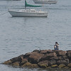 Beverly:<br /> A woman sits at the end of the rock breakwater at Independence Park in Beverly on a hot and hazy Tuesday afternoon.<br /> Photo by Ken Yuszkus/Salem News, Tuesday August 17, 2010.