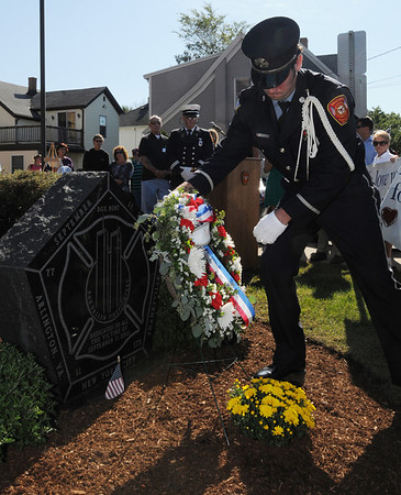Danvers:<br /> Lt. Michael Graves, Danvers firefighter, places a wreath near the 9/11 monument during the 9/11 ceremony in front of the Danvers Fire Department Sunday morning. <br /> Photo by Ken Yuszkus/Salem News, Sunday, September 11, 2011.