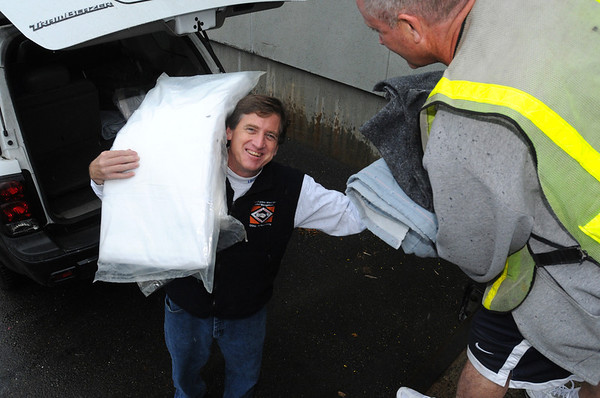 Middleton:<br /> Mark Brings hands a stack of blankets to Michael Lovett, inmate, while unloading his vehicle. Mark Brings, his wife, Janet, and daughter, Erin, brought blankets and sheets to the Middleton Jail to be washed before sending them to an orphanage in Afghanistan.<br /> Photo by Ken Yuszkus/Salem News, Wednesday, October 19, 2011.