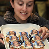 Danvers:<br /> Lynne Sheeley, marketing coordinator at Cakes For Occasions, holds a tray of cupcakes made with the likeness of Olympian Meghan Duggan. The cupcakes were made at Cakes For Occasions.<br /> Photo by Ken Yuszkus/Salem News, Wednesday, February 24, 2010.