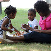 Peabody:<br /> From left, Savanah Muasya, 3, Tyler Davis, 3 1/2, and Winnie Muasya, all of Peabody, enjoy their picnic lunch in the shade at the end of summer celebration held at Emerson Park. The Peabody Institute Library, Main Branch hosted a free picnic lunch with kites given to the children before a talk and demonstration by Todd Brodeur, 2-Time Freestyle Frisbee World Champion. <br /> Photo by Ken Yuszkus/The Salem News, Wednesday, August 22, 2012.