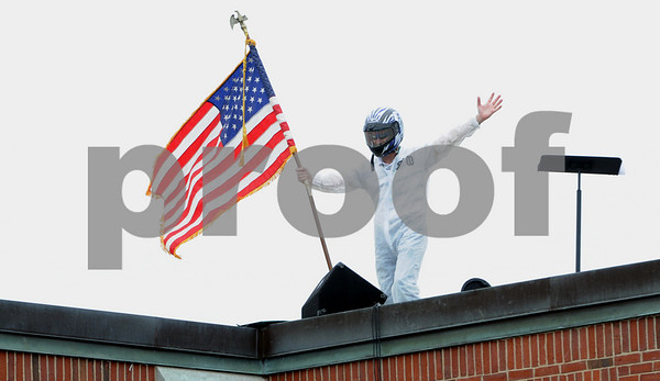 Danvers:<br /> Principal Matt Fusco plants the flag on the roof where he landed after blasting off in a rocket from inside the Great Oak School gym. <br /> Photo by Ken Yuszkus/Salem News, Friday, June 5, 2009.