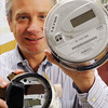 Danvers:<br /> David Lane holds a new water meter, left, and new electric meter that will be now used in Danvers. 13,000 meters will be installed in homes this year.<br /> Photo by Ken Yuszkus/Salem News, Friday, December 9, 2011.