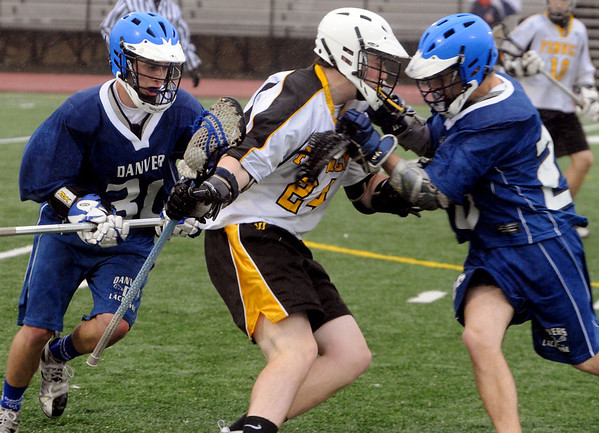 Danvers:<br /> From left, Danvers #30 tries to take the ball away from Bishop Fenwick #24, with the help of Danvers #26 at the Danvers at Bishop Fenwick boys lacrosse game.<br /> Photo by Ken Yuszkus/Salem News, Tuesday,March 30, 2010.