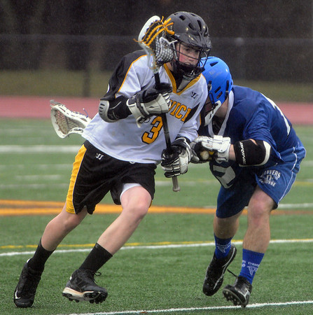 Danvers:<br /> Bishop Fenwick #3, runs with the ball as Danvers #12 nudges him from the side at the Danvers at Bishop Fenwick boys lacrosse game.<br /> Photo by Ken Yuszkus/Salem News, Tuesday,March 30, 2010.