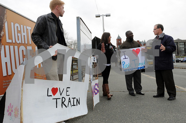 Salem:<br /> From Left, Kyle Webster, MASSPIRG Salem State College student, Meagan Terry, MASSPIRG campus organizer, but not a student, and Lawrence Gleekia, MASSPIRG Salem State College student, speak with Rep. John Keenan before presenting the train cutout to him at the Salem train station as thanks for his support of public transit in Salem.<br /> Photo by Ken Yuszkus/Salem News, Thursday November 5, 2009.