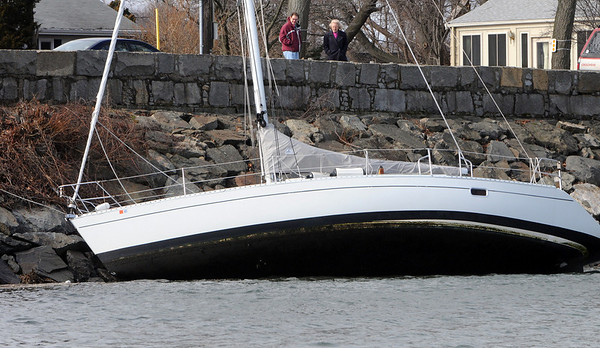 Salem:<br /> People view the sailboat that washed ashore in Salem Harbor near Lafayette Street.<br /> Photo by Ken Yuszkus/Salem News, Friday, February 26, 2010.