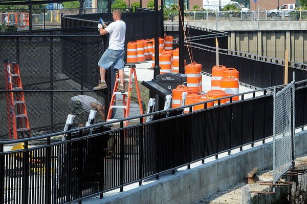 Salem:<br /> Mark Lapierre on the ladder and John Christopher install fencing along the Harbor Walk. Harbor Walk will open on Thursday with a ribbon cutting ceremony. <br /> Photo by Ken Yuszkus/Salem News, Tuesday, July 13, 2010.