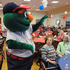 Peabody:<br /> Wally the Green Monster waves as he enters and wanders through crowd at the McIntosh Clubhouse at Brooksby Village. He was part of the opening day pep rally festivities held Thursday at noon at Brooksby Village. The rally featured Wally the Green Monster, Red Sox trivia contests, a contest for the five best Red Sox outfits and lots of cheering, singing, and Fenway Franks. <br /> Photo by Ken Yuszkus/Salem News, Thursday, April 7, 2011.