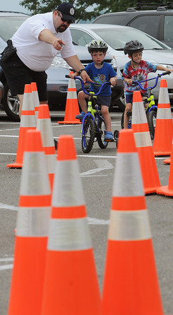 Beverly:<br /> Salem police officer Ted Goodell instructs Andrew Dunleavy, 3, how to maneuver through the obstacle course during the Bicycle Safety Rodeo at Lynch Park. The Beverly Kiwanis Club and Beverly Police Department sponsored the annual Bicycle Safety Rodeo as part of the Beverly Homecoming.<br /> Photo by Ken Yuszkus/Salem News, Monday, August 1, 2011.