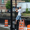 Salem:<br /> Mark Lapierre, on the ladder, installs fencing along the Harbor Walk. Harbor Walk will open on Thursday with a ribbon cutting ceremony. <br /> Photo by Ken Yuszkus/Salem News, Tuesday, July 13, 2010.