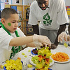 Salem:<br /> Brandon Bass, Celtics forward, right, watches Richard Jiminez, student of Bailey Malone's third-grade class at the Bates Elementary School, build a presentation fruit plate with fellow students. Rajon Rondo, Celtics point guard, Bryan Doo, Celtics strength and conditioning coach, and Lucky, the Celtics mascot, were also present. They were there for the program promoting a healthy and active lifestyle. <br /> Photo by Ken Yuszkus/Salem News, Thursday,  March 8, 2012.