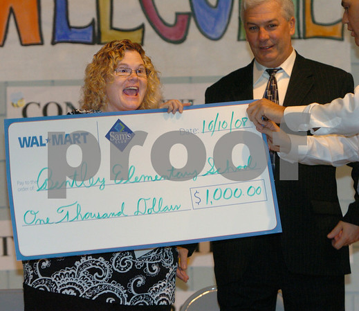Salem:<br /> Left, Carla Meagher, an integrated kindergarten teacher at the Bentley School, reacts to being awarded the Walmart teacher of the year award in front of the students and faculty at the school. The honor includes a check of one thousand dollars. She received the check from, Shawn Rasco, far right, store manager from the Salem Walmart. Carla's husband,Thomas Meagher, is in the center. <br /> Photo by Ken Yuszkus/Salem News, Friday October 10, 2008.
