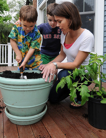 Hamilton:<br /> From left, Kyle, 4, Brady, 5, and their mother, Jennifer Daniels, dig a hole to plant a tomato plant,  right, into a large pot on the deck at their home.<br /> Photo by Ken Yuszkus/Salem News, Thursday, May 19, 2011.