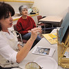 Beverly:<br /> Martha Dooling, instructor, left, demonstrates a painting technique with acrylic paint on Norma Savlon's canvas board during a painting class at the Beverly Council on Aging on Wednesday afternoon.<br /> Photo by Ken Yuszkus/Salem News, Wednesday, January 26, 2011.