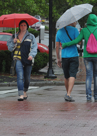 Salem:<br /> Olga Skliar, a tourist from Canada, walks across Norman Street clutching her umbrella passing a couple with another umbrella during the rain.<br /> Photo by Ken Yuszkus/Salem News, Monday, June 25, 2012.