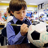 Salem:<br /> Max McAuliffe, Second grader at Horace Mann Laboratory School, dreamed up the community service project to sign soccer balls and donate the soccer balls to earthquake victims in Haiti. He is darkening his signature by to make it bolder.<br /> Photo by Ken Yuszkus/Salem News, Wednesday, March 3, 2010.