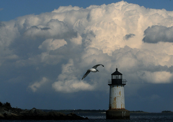 Salem:<br /> A seagull heads toward the lighthouse at Winter Island as a cloud mass forms in the background. Although warm today, cool weather is forcast for the next few days.<br /> Photo by Ken Yuszkus/Salem News, Tuesday,  September 14, 2010.
