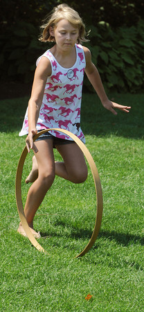 Salem:<br /> Annabelle Vance, 9, rolls a hoop by hand while playing the 400 year old game of hoop and stick during the Lawn games at the House of 7 Gables as part of Heritage Days. She is from Hope, New Jersey.<br /> Photo by Ken Yuszkus/The Salem News, Thursday, August 9, 2012.