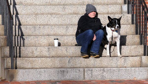 Salem:<br /> Virginia Penziner and her dog Micah sit in the warm sunshine on the granite steps of Salem Old Town Hall protected from the wind and cold.<br /> Photo by Ken Yuszkus/Salem News, Wednesday, January 4, 2011.