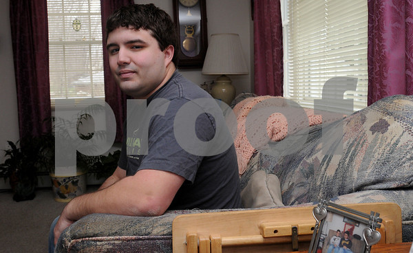 Beverly:<br /> Aaron Shaw does not own a cell phone. He is sitting on a sofa at his home.<br /> Photo by Ken Yuszkus/Salem News, Wednesday, April 8, 2009.