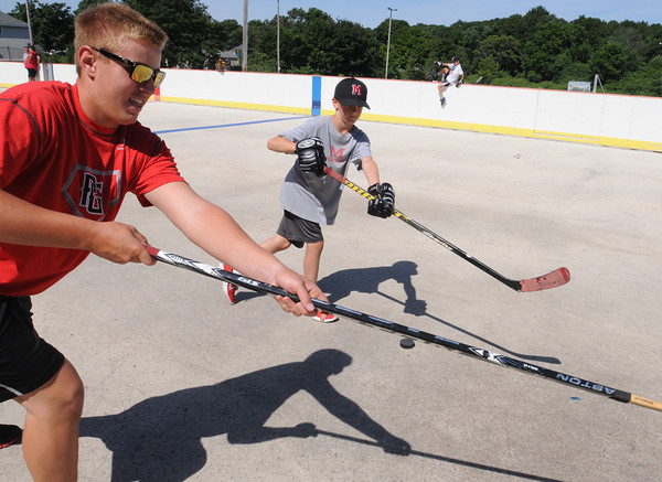 Marblehead:<br /> Tom Koopman, left, of the Marblehead High varsity hockey team, coaches Ryan Tarmey, 11,  at the Dry Land Hockey Training camp in Marblehead for boys and girls in grades 2-8 held at the Bud Orne Memorial Rink. They were assisted by coaches as well as members of the Marblehead High varsity hockey team.<br /> Photo by Ken Yuszkus/Salem News, Tuesday, August 7,  2012.