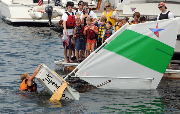 Marblehead:<br /> Robbie Segee rights the sailboat after deliberately capsizing it in Marblehead harbor at the Boston Yatch Club. The exercise was a test to join the Boston Yatch Club Junior Sailing Program. <br /> Photo by Ken Yuszkus/Salem News, Monday, June 28, 2010.