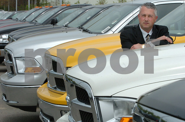 Danvers:<br /> Jim Klimas, general manager at Herb Chambers Chrysler Jeep Dodge of Danvers, stands by a line of  2009 Dodge Ram trucks on the lot of the dealership.<br /> Photo by Ken Yuszkus/Salem News, Monday May 4, 2009.