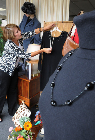 Beverly:<br /> Jan Rink, store volunteer and fashion show co-ordinator, adjusts the necklace on the dress in the window display at Boots, Straps and More thrift shop. Bootstraps Community Services is partnering with the Beverly Senior Center to stage a fashion show on Sept. 13 using clothes that have been donated to the Bootstraps thrift shop. <br /> Photo by Ken Yuszkus/Salem News, Thursday,  September 9, 2010.