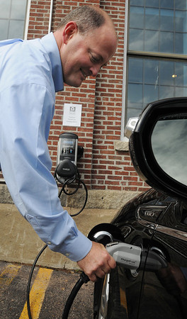 Ipswich:<br /> Tom Wheeler, CFO of EBSCO, plugs the power cord from the electric vehicle charging station into a Chevy Volt. It is one of two stations at EBSCO. <br /> Photo by Ken Yuszkus/Salem News, Wednesday, August 10, 2011.