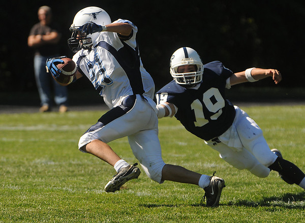 Danvers:<br /> Peabody's Brady Doyle gets by St. John's Prep Mark MacDonald's reach during the Peabody at St. John's Prep football game at Cronin Stadium. It was the season opener for both teams.<br /> Photo by Ken Yuszkus/Salem News, Saturday,  September 11, 2010.