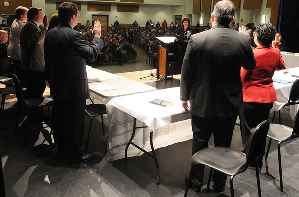 Beverly:<br /> Kathleen Connolly, Beverly city clerk, gives the oath of office to the school committee on the stage during the inauguration ceremony at Beverly High School.<br /> Photo by Ken Yuszkus/Salem News, Tuesday, January 3, 2011.