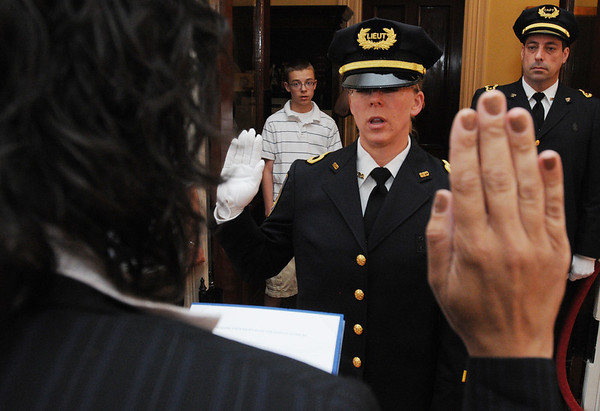 Salem:<br /> Salem Mayor Kim Driscoll, left, administers the oath to Kate Stephens who was promoted to lieutenant of the Salem Police Department. In the background looking on is Kate's son, Thomas, left, and Captain Mark Losolfo, who was also sworn in as a new captain.<br /> Photo by Ken Yuszkus/Salem News, Thursday, July 7, 2011.
