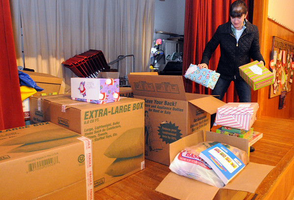 Boxford:<br /> Sue Rubin of Community Giving Tree, sorts out Friendship Boxes from the Tower School in Marblehead. The boxes are some of the many items that volunteers will be setting up for the open house, which is on Wednesday. At the open house at the Second Congregational Church, social service workers from all of Essex County will be able to chooseÊnew toys, coats in adult and children' s sizes, children's clothes, toiletries, and diapers for their clients.Ê<br /> Photo by Ken Yuszkus/Salem News, Tuesday, December 15, 2009.