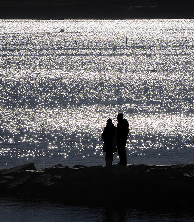 Beverly:<br /> A couple stand on the rock breakwater at Independence Park as the sun sparkles off the ocean in the background on a cold sunny morning.<br /> Photo by Ken Yuszkus/Salem News, Friday, February 4, 2011.