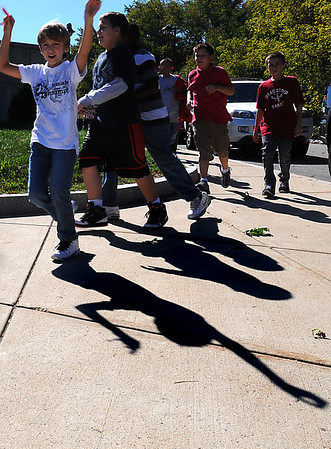 Salem:<br /> Shadows dance along side of the students walking around the Witchcraft Heights Elementary School during the 22nd annual walkathon, run by the PTO, which helps pay for student activities and programs.<br /> Photo by Ken Yuszkus/Salem News, Friday,  October 8, 2010.