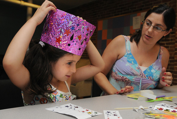 Salem:<br /> Elizabeth Connell, 5, and her mother Tina McConnell of Salem create a crown at the arts and crafts table during the Kids Night on the Common which is part of Heritage Days. Rain forced the event inside the Salem YMCA instead of holding it on the Salem Common.<br /> Photo by Ken Yuszkus/The Salem News, Friday, August 10, 2012.