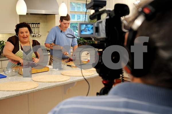 Beverly:<br /> Left, Angela Dominick, and Rob Worsley, demonstrate cooking during the La Cucina Famiglia cooking show being shot in a Beverly kitchen for an upcoming episode.<br /> Photo by Ken Yuszkus/Salem News, Monday, August 3, 2009.