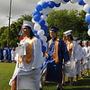 Danvers:<br /> Graduates Audrey Bekeritis and Charles Bramesco lead one of the lines of graduates through the balloon arch during the processional of the Danvers High School graduation at Dr. Deering Stadium. <br /> Photo by Ken Yuszkus/Salem News, Monday, June 13, 2011.