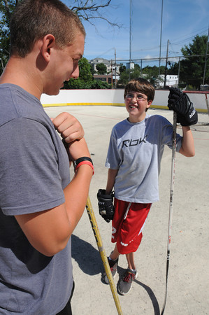 Marblehead:<br /> Liam Gillis, left, of the Marblehead High varsity hockey team, speaks with Brendan Locke, 11, at the Dry Land Hockey Training camp in Marblehead for boys and girls in grades 2-8 held at the Bud Orne Memorial Rink. They were assisted by coaches as well as members of the Marblehead High varsity hockey team.<br /> Photo by Ken Yuszkus/Salem News, Tuesday, August 7,  2012.