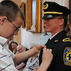 Salem:<br /> Kate Stephens was promoted to lieutenant of the Salem Police Department and her son, Thomas, pins the new designation of rank on her.<br /> Photo by Ken Yuszkus/Salem News, Thursday, July 7, 2011.