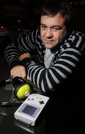 """Salem:<br /> Scott Buchanan, a dj and """"chip tune"""" musician, who uses hand-held gameboys and video game systems to make music. A gameboy is in the foreground.<br />  Photo by Ken Yuszkus/Salem News, Monday November 30, 2009."""