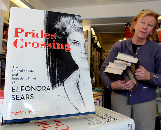 """Beverly:<br /> Lalie Clayman, sales associate at The Book Shop of Beverly Farms, stands near a stack of """"Prides Crossing"""" books. """"Prides Crossing,"""" is a book of nonfiction about a Beverly woman that was published by a North Shore publisher, Commonwealth Editions.<br /> Photo by Ken Yuszkus/Salem News, Thursday, December 17, 2009."""