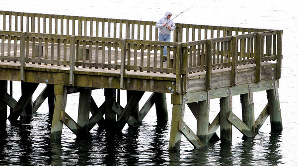 Beverly:<br /> A fisherman tries his luck fishing off the pier on a gray Monday morning.<br /> Photo by Ken Yuszkus/Salem News, Monday, April 26, 2010.
