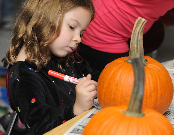 Salem:<br /> Evelyn Buxton, student at the Bates School, decorates her pumpkin during the after school program at Bates School. The students are decorating pumpkins for Salem's annual Pumpkin Decorating Contest. The pumpkins were donated by the Salem Beautification Commitee.<br /> Photo by Ken Yuszkus/Salem News, Thursday, October 14, 2010.