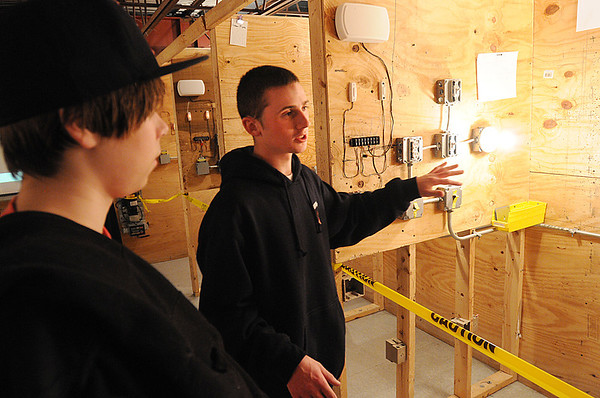 Middleton:<br /> Ian  Lefavour, electrical student, right, explains the electrical program to Eddie Basso, of Gloucester, who is visiting NorthShore Tech's Open House on Thursday evening.<br /> Photo by Ken Yuszkus/Salem News, Thursday, November 10, 2011.