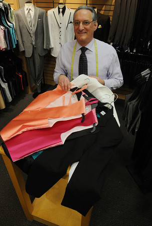 Danvers:<br /> Larry Levine, manager of Men's Warehouse at Liberty Tree Mall, shows some vests and bow ties in  popular colors while standing near tuxedos that the store rents.<br /> Photo by Ken Yuszkus/Salem News, Monday, May 14, 2012.